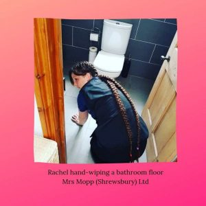 Mrs Mopp Shrewsbury Domestic Moppette Rachel cleaning the bathroom floor of a clients home on her hands and knees. Rachel has very long hair in french braids across her back and is looking towards to camera | Mrs Mopp UK