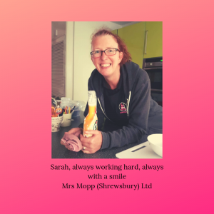 Mrs Mopp Shrewsbury domestic Moppette Sarah leaning on a kitchen side, holding a microfiber cloth and a bottle of cleaning solution